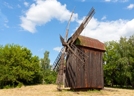 old windmill on rural meadow in summer day photo