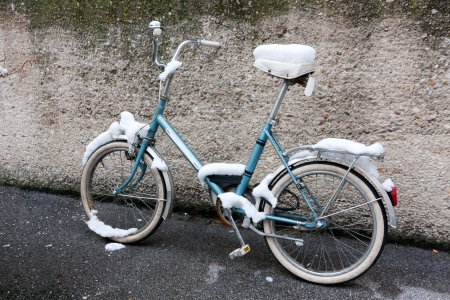 bike in snow near wall photo
