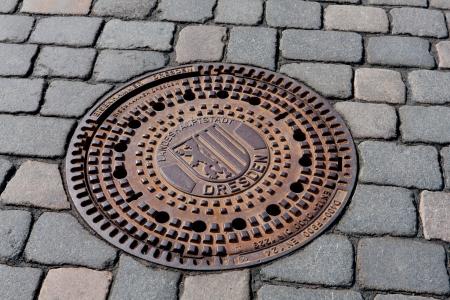 Round steel sewer manhole on pavement in Dresden