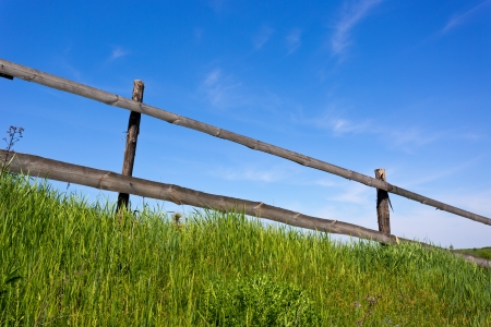 wooden fence on grassland with blue sky