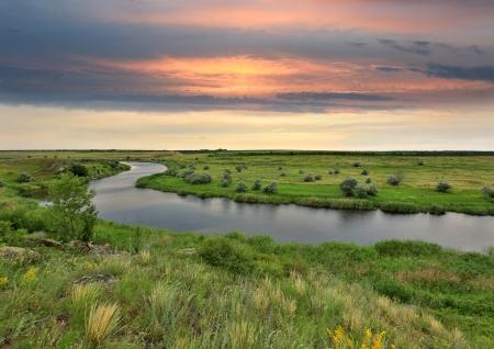 Landschap met rivier in steppe voor de regen op zonsondergang Stockfoto