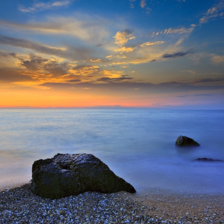 Stones in sea water on sunset background photo