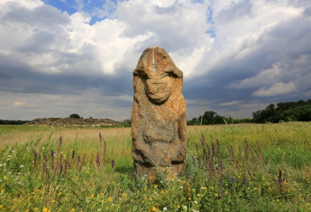 mounds: stine idol in steppe on stormy sky background