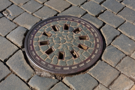 manhole on pavement in sunny day photo
