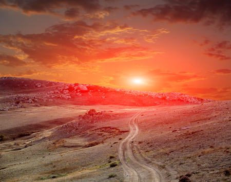 road in mountains on sunset in sky photo