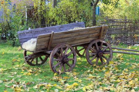 Wooden carriage in autumn garden Stock Photo - 23139480