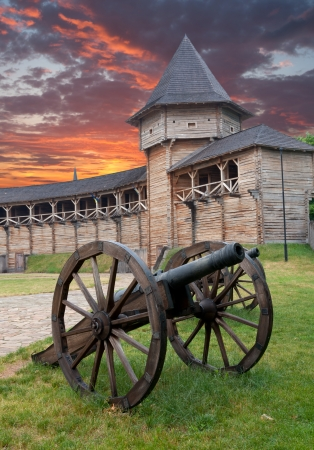 Gun in old wooden fortress Stock Photo