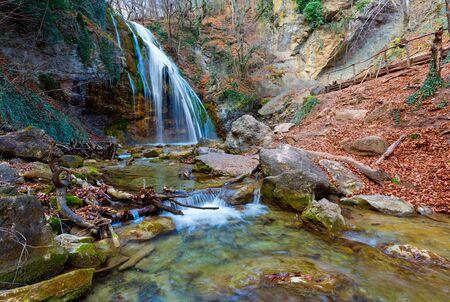 autumn scene with waterfall in mountain gorge photo