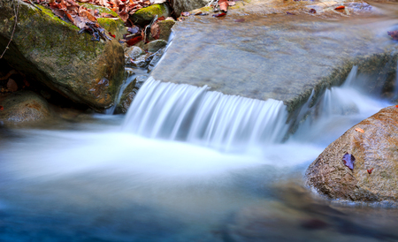 small waterfall on mountain stream photo