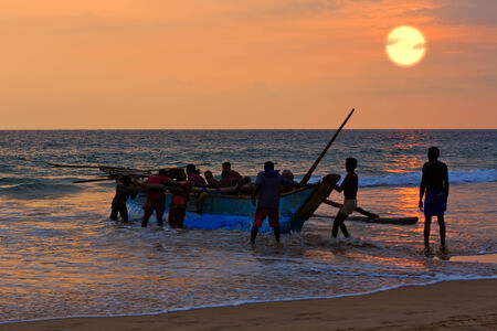boat and fishers on sunset
