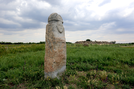 Stone idol in steppe before thunder Stock Photo