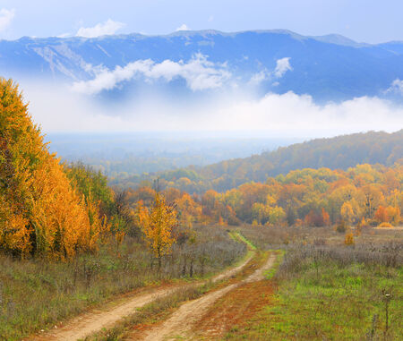 rut: rut road in autumn forest against mountains in clouds background