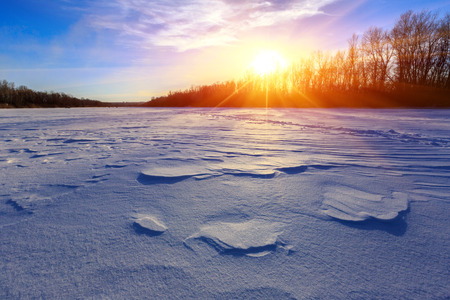blue snow on vinter meadow against sunset photo