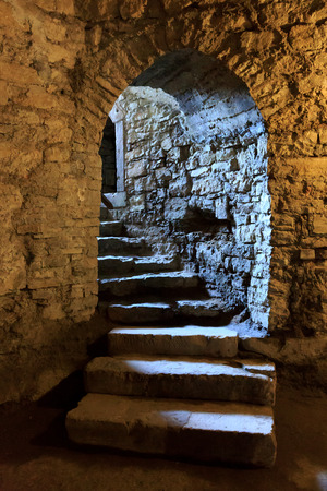 dungeons: Stone arch and steps in underground castlte Stock Photo
