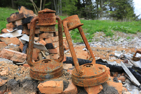 two old oil lantern on ruines after fire disaster