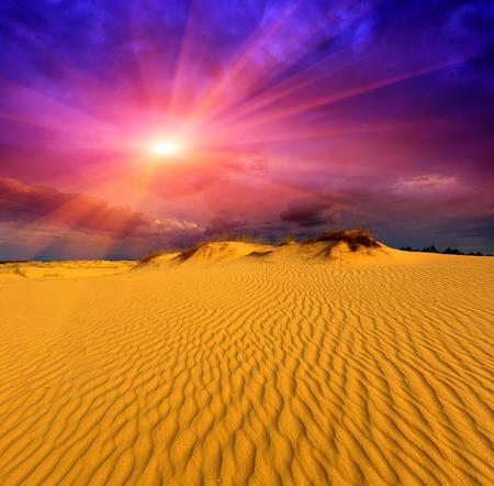 Sunset in desert over yellow sand Stock Photo