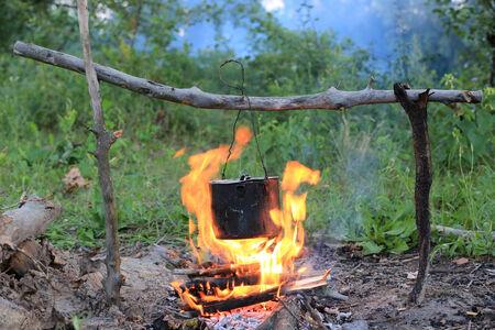 smoked tourist kettle on camp fire Standard-Bild