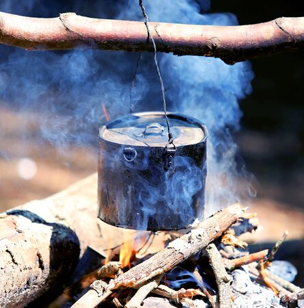 tourist kette over campfire with blue smoke photo