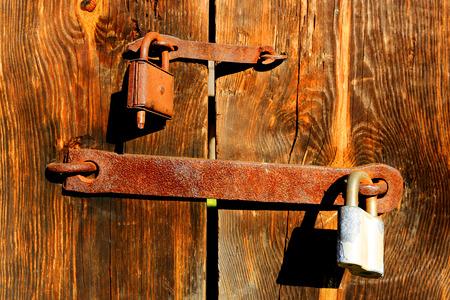 Old two rusty locks on wooden door   photo