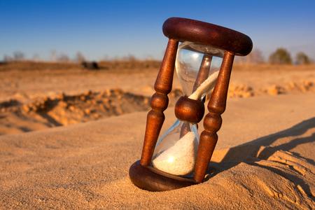 scene with hourglass in desert's sand