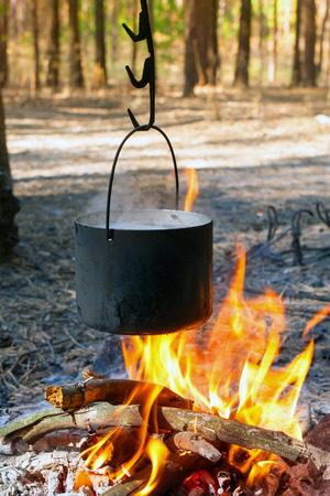 Tourist kettle over hot camp fire photo