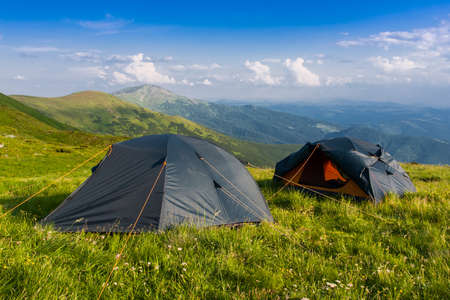 refuge: Two tourist tents among green meadow in mountains