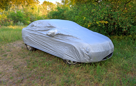 car with cover in forest meadow Standard-Bild