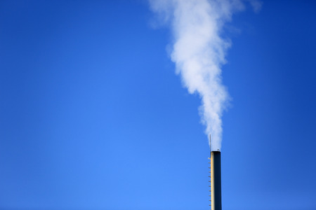 Flue with smoke on blue sky background