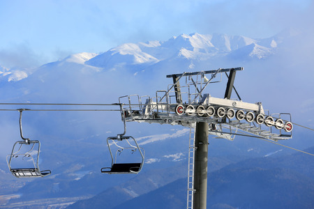 chairlift: Chairlift on winter ski resort against mountain background