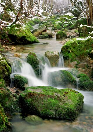 wild silky white: small waterfall on winter mountain stream