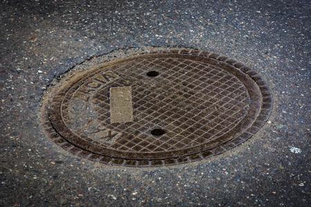 Abstract manhole cover on asphalt pavement photo