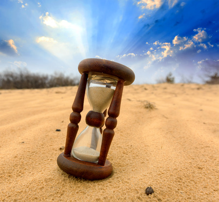 Old Hourgass in desert on sand