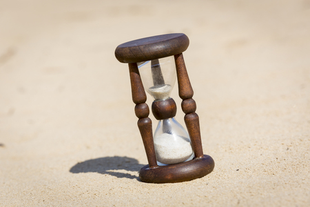 Old Hourglass in desert on sand photo