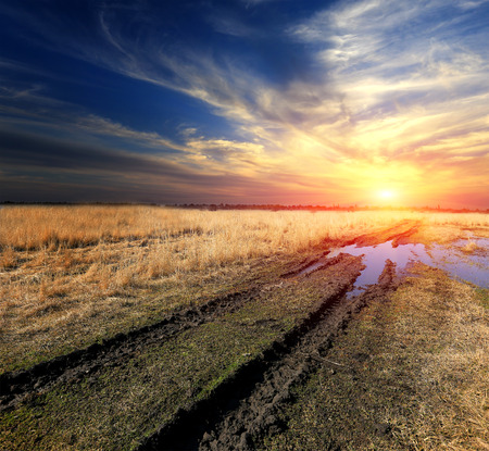 Rut dirt road across steppe after rain against sunset sky background Stock Photo