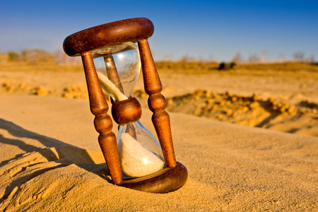 hourglass in desert sandy surface