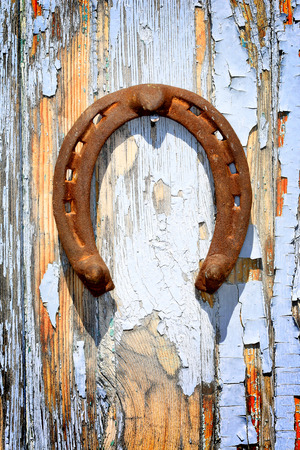 old horseshoe on old wooden wall Фото со стока