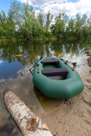 inflatable boat: Nice inflatable boat on lake shore in summer forest Stock Photo