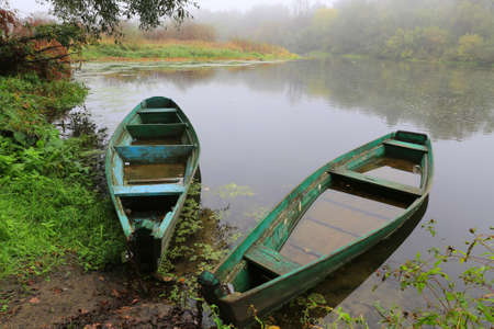 flooded: old flooded wooden boats on river