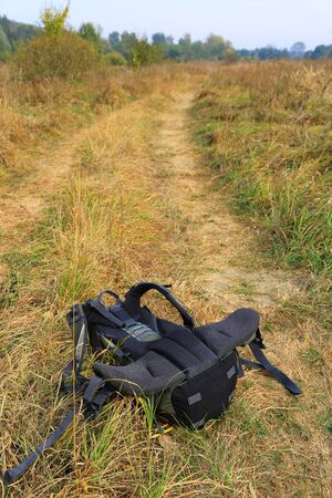 meadow  grass: Tourist backpack on dry meadow grass
