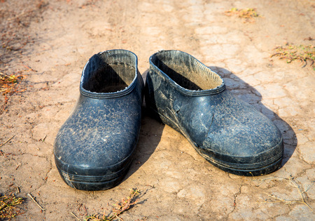 galoshes: old lost galoshes on dry soil Stock Photo