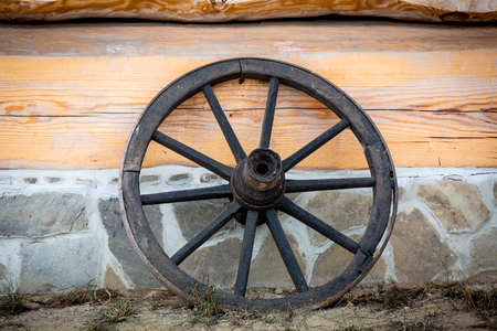 wheel house: wooden wheel on rural house wall background Stock Photo