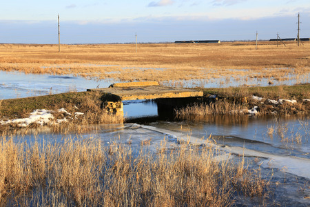 cane creek: old bridge on rut road in steppe at early spring time