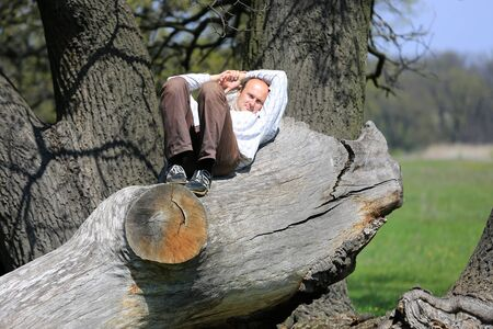 rest day: Man rest on old tree at spring day Stock Photo