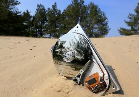 gigabytes: lost broken computer disk on sand in forest