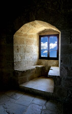 through window: view from old fortress through window on sky with clouds Stock Photo