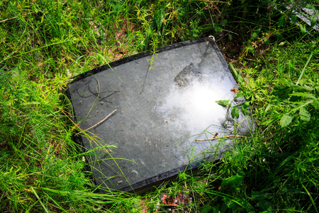 broken television tube among green grass on meadow Stock Photo