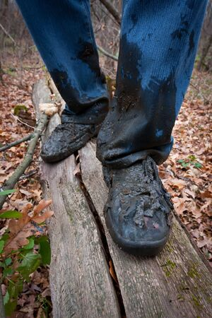 miry: boots men in the dirt on a log in the autumn forest