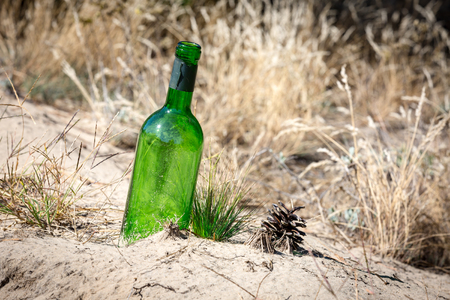 negligent: lost green bottle among sand in forest