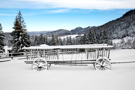 old wood farm wagon: old wooden carriage in snow on winter meadow