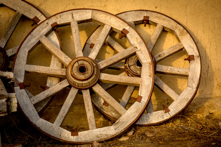 adobe wall: Old wooden wheels from cart Stock Photo